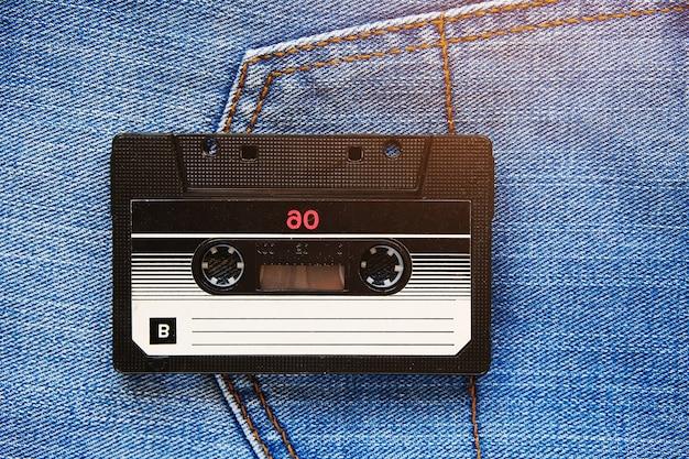 Vintage retro audio cassette on the of blue jeans