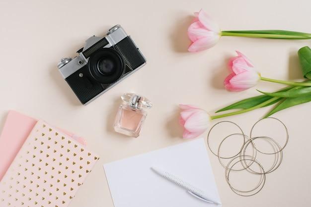 베이지색 배경에 빈 노트북이 있는 빈티지 복고 카메라와 분홍색 튤립 꽃. 여성 블로거 플랫 레이. 평면도. 봄 개념을 조롱합니다.