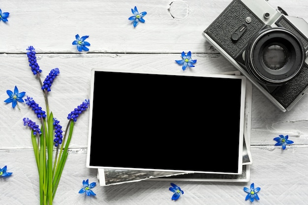 Vintage retro camera, blank photo frame and spring blue flowers