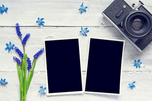 Vintage retro camera, blank photo frames and spring blue flowers