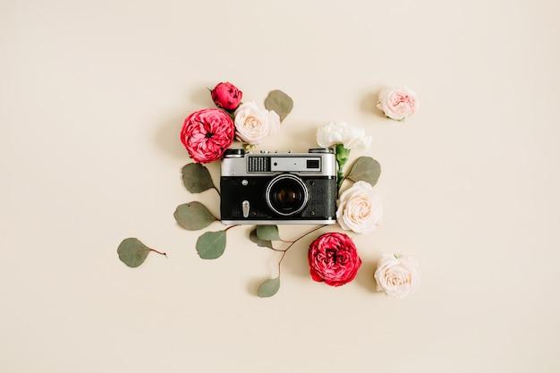 Винтажная ретро камера, красные и бежевые бутоны розы на бледно-пастельных бежевых фоне. плоская планировка, вид сверху