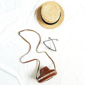 写真カメラ、麦わら帽子、白い表面のメガネとヴィンテージのレトロなコンセプト