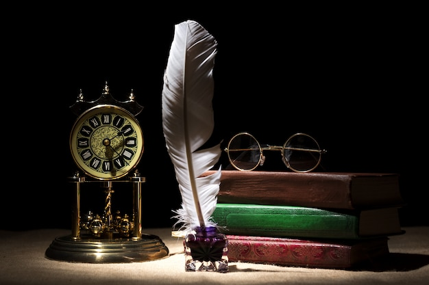 Vintage retro glasses on old books near inkstand with feather and old clock against black background
