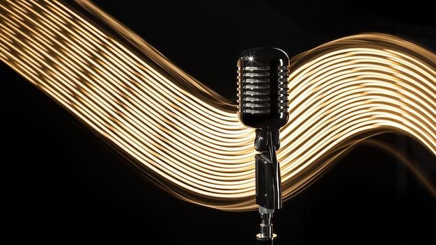 Винтажный ретро микрофон на черном фоне со световой волной