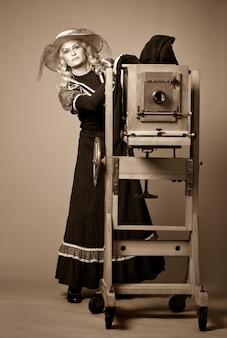 灰色の背景にダゲレオタイプのビンテージカメラの近くに立っている長い控えめなドレスと帽子の若い女性のビンテージレトロなスタイルの写真。レトロな写真とヴィンテージのコンセプト。