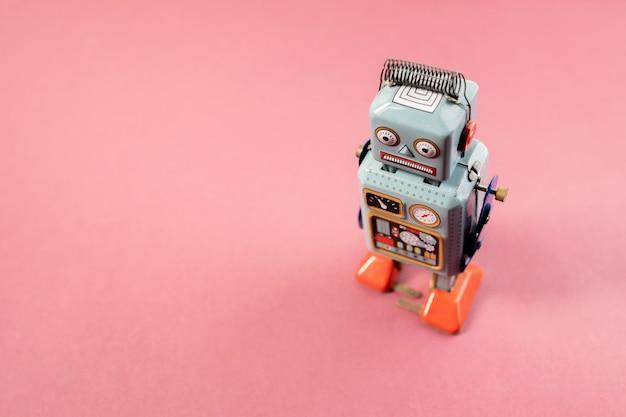 Старинная игрушка из олова робота на розовом фоне