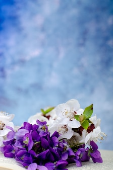 Vintage romantic background with old book, violet flowers and copy space.