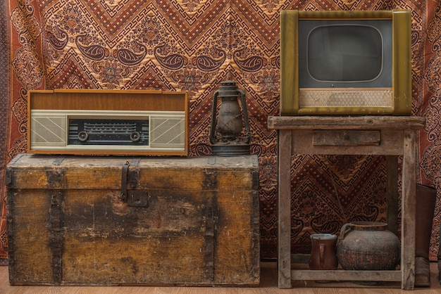 古いラジオ、アンティークのビンテージランプ、古い壁紙を背景にしたレトロなテレビのあるビンテージルーム