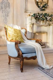 白い暖炉、キャンドル、モミの枝、装飾とビンテージルーム。ビンテージアームチェア、暖炉のある明るいスタイリッシュなリビングルームのクリスマス装飾。美しい装飾が施された暖炉