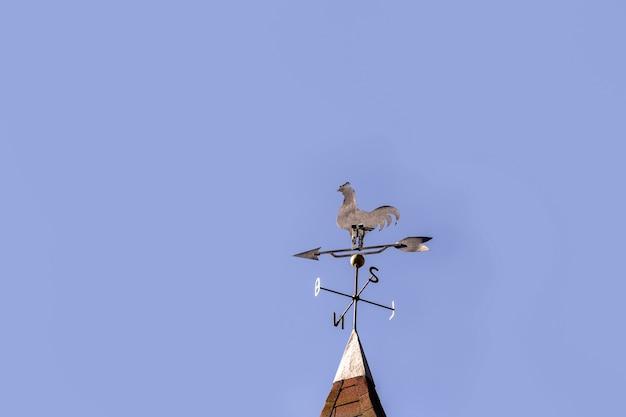 ヴィンテージのオンドリの風見鶏、北、南、東、西の枢機卿のポイント、表面に青い空があります