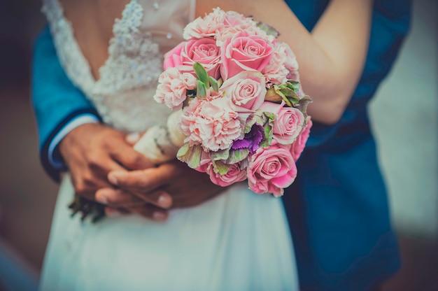 新婚女性の手にヴィンテージのバラの花束