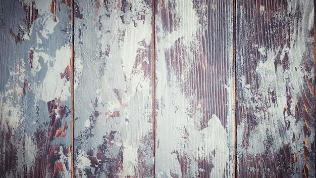 배경에 회색 페인트 패치가 있는 빈티지 거친 갈색 나무 질감