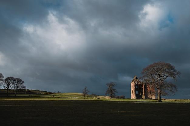 Винтаж разрушенный замок 17 века в поле перед ливнем, замок гилбертфилд, глазго, южный ланаркшир, шотландия