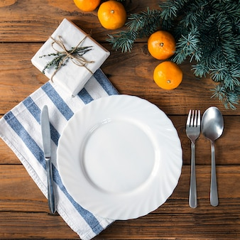 Vintage or rustic christmas table setting from above. elegant empty white plate, cutlery on linen napkin and natural pine tree branch on rustic planked woodcountry style.