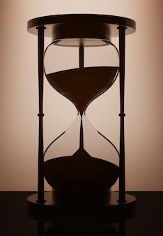 Винтажные песочные часы с подсветкой над стеной в темной комнате. 3d рендеринг