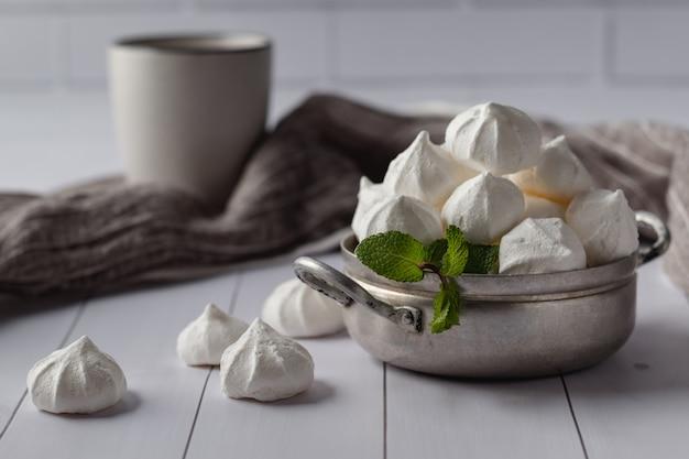 白い木製のテーブルにキスバニラメレンゲとビンテージ鍋