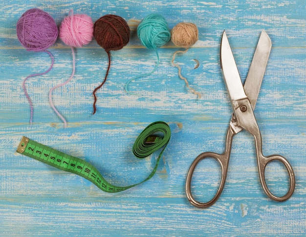 Vintage scissors, balls of wool and tape measure on a blue wooden table.