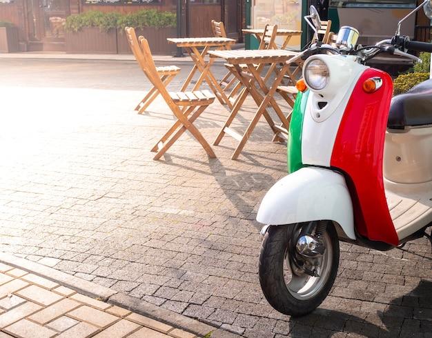 Винтажный скутер цвета итальянского флага на солнечной площади недалеко от уличного кафе