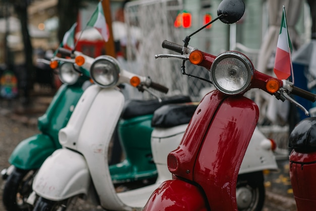Vintage scooters on a city street near an italian restaurant
