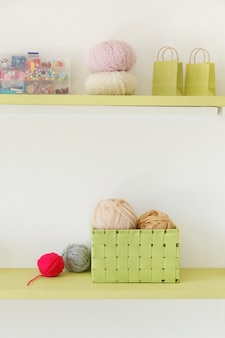 Vintage shelves with knitting tools with woolen balls and buttons