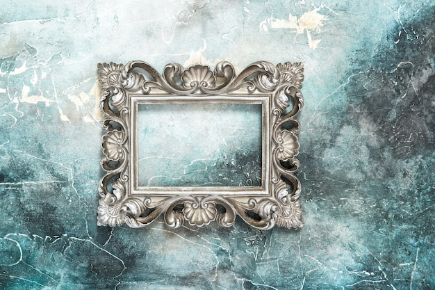 Vintage silver baroque style picture frame on stone background