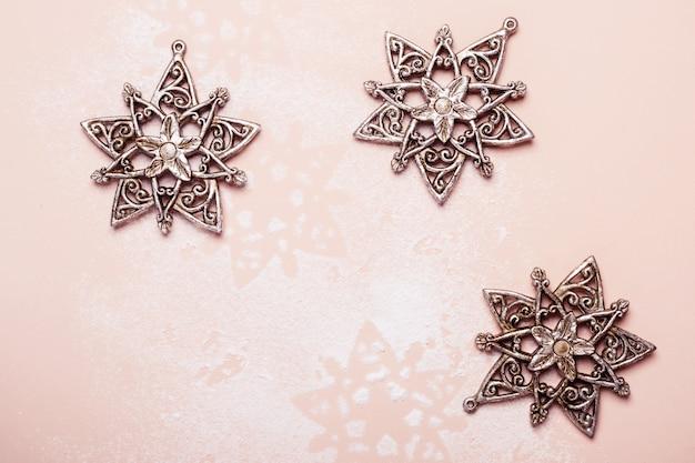 Винтажные серебряные рождественские игрушки снежинки на розовом фоне.