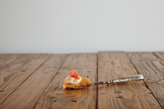 Винтажная серебряная вилка на грубом деревянном столе с кусочком бисквитного торта со сливками и грейпфрутом