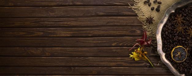 Старинный серебряный поднос с кофейными зернами, специями и цветами на столе