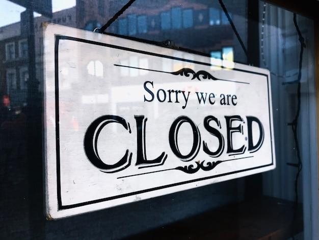 Vintage sing sorry we are closed sign hangs in shop door