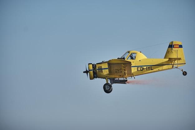 完全に澄んだ青い空を飛んでいるプロペラを備えたヴィンテージの単発機