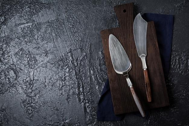 어두운 돌 또는 콘크리트 배경에 케이크 빈티지 주걱과 칼