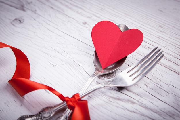 Vintage spoon and fork with a red tape and heart for valentine's day on a wooden table.