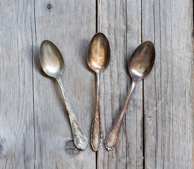 Vintage spoons with patina on wood top view