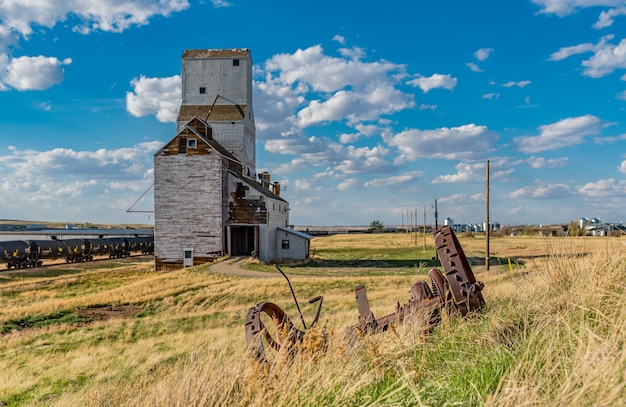 Vintage steel wheels from a farming implement with the historic grain elevator in sanctuary, saskatchewan
