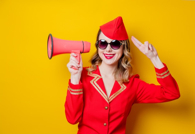 Vintage stewardess wearing in red uniform with megaphone