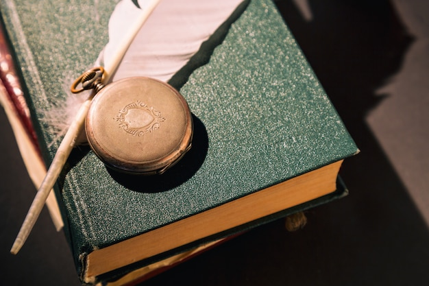 Vintage still life with clock on old books near feather or quill. close up