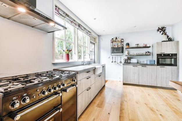 Старинная печь под вытяжкой возле шкафов с раковиной у окна и двери в светлой кухне дома