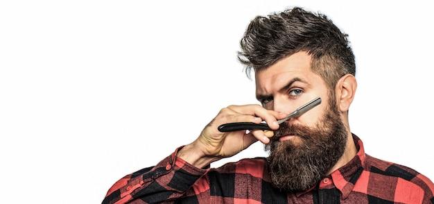 Винтажная опасная бритва. мужская стрижка в парикмахерской. парикмахерская опасная бритва, парикмахерская. бородатый мужчина, длинная борода, брутальный, кавказский хипстер с усами. место для текста.