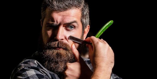 Винтажная опасная бритва. мужская стрижка. мужчина в парикмахерской.
