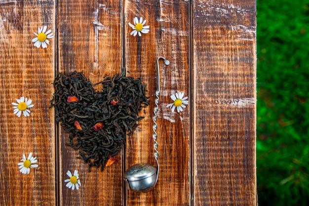 紅茶の乾燥した葉の近くのビンテージストレーナーは、木製のテーブルに心で作る