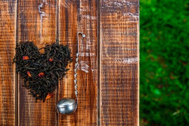 紅茶の乾燥した葉の近くのビンテージストレーナーは、木製のテーブルの中心に作る