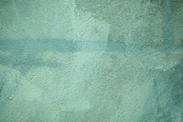 Vintage style fading forest green wall  texture with rough cement surface in a full frame view.