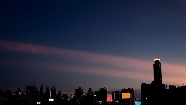 ヴィンテージスタイルのモダンな都市の複雑な建物超高層ビルのスカイライン暗い夕日のパノラマ空中写真