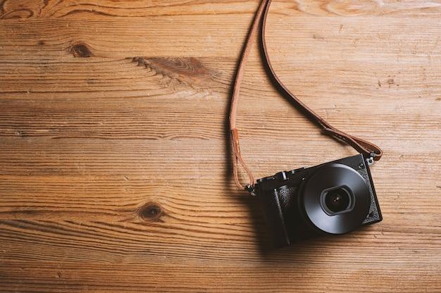 나무 배경에 분리된 가죽 스트랩이 있는 빈티지 스타일의 디지털 미러리스 카메라