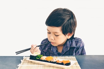 Vintage style photo of asian lovely boy is eating sushi