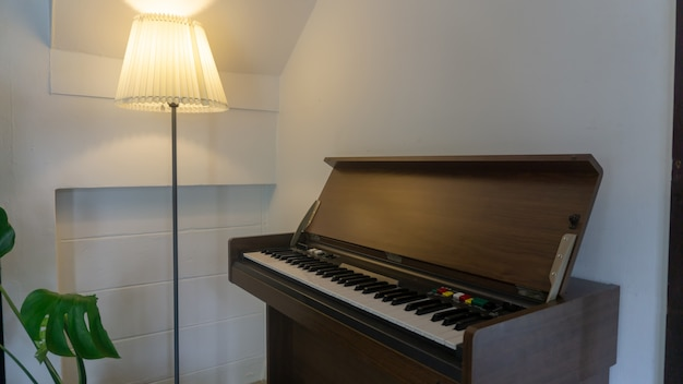 Vintage style piano in the conner of room with lamp