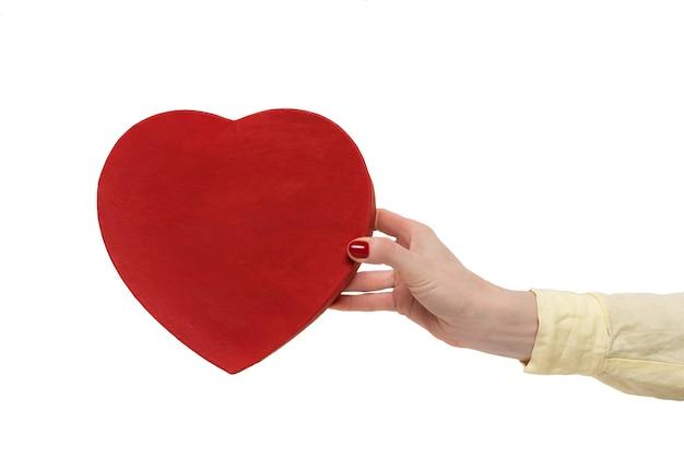 Коробка в форме сердца в винтажном стиле красная на женской руке, изолированные на белом фоне. передний план.