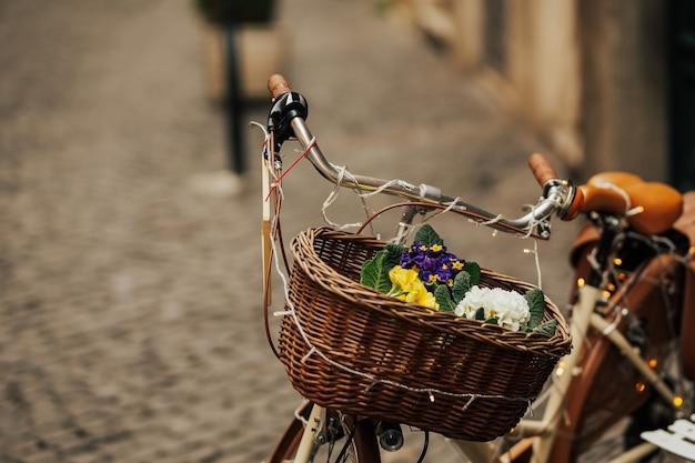装飾として花のバスケットを持つ古い自転車のビンテージ様式化された写真。