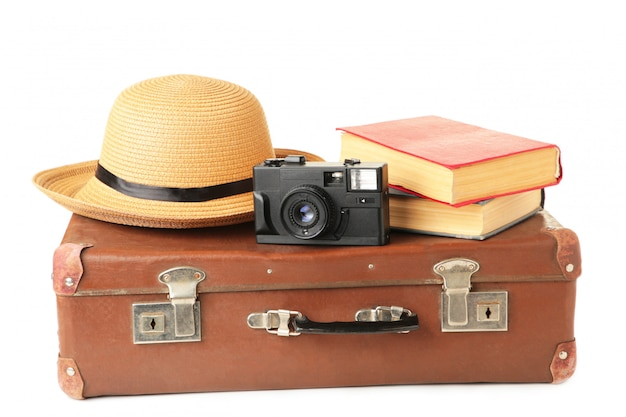 Vintage suitcase and accessories isolated on white wall