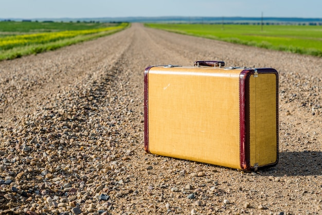 Vintage suitcase in the middle of a country road on the prairies